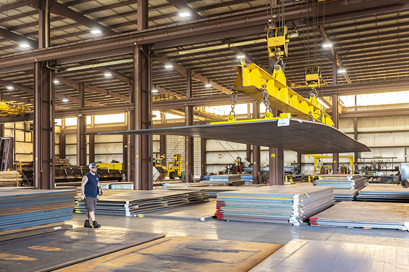 A warehouse employee moves steel plate using a crane